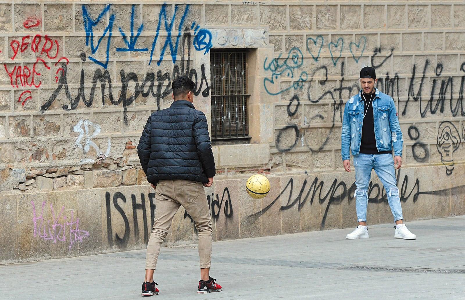 Dos nois immigrants juguen a pilota al carrer de les Floristes de les Rambles al Raval. ©Xavier Jubierre