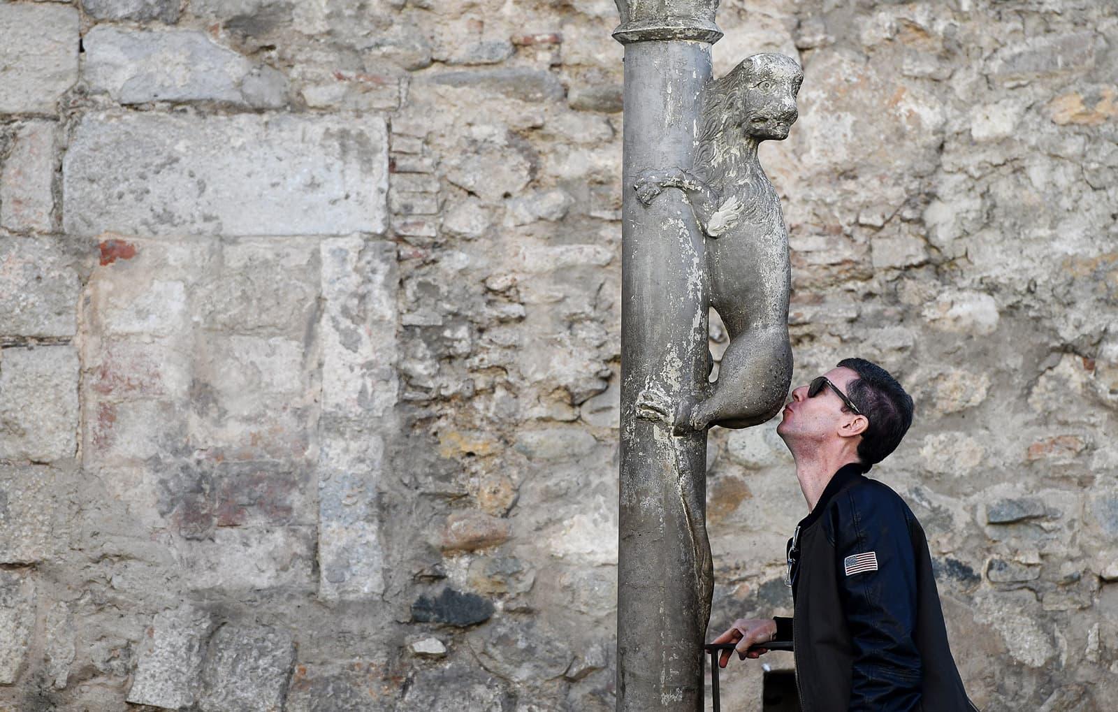 Un turista compleix amb la tradició de fer un petó al cul de la lleona de la plaça de Sant Feliu de Girona. Fotografia de Xavier Jubierre.