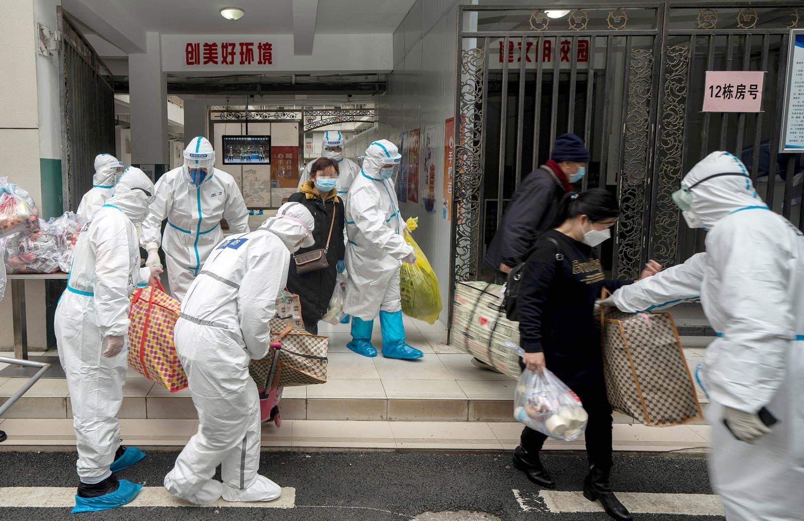 Pacients, que han complert la quarantena, surten del centre d'internament de Wuhan envoltats de grans mesures sanitàries, avui. Fotografia de Fei Maohua/Imago images
