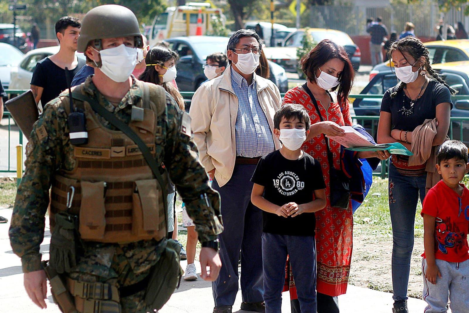 Cues de persones, a Santiago de Xile, per rebre la vacuna de la grip que ha coincidit amb l'estat d'emergència pel coronavirus, el 20 de març. Fotografia de Sebastián Silva/Efe