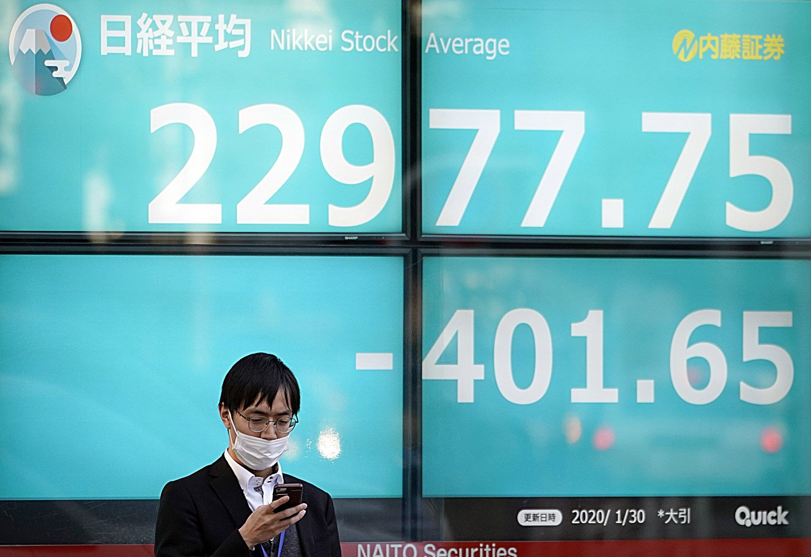 Un trabajador de la bolsa de Tokio con mascarilla el 30 de enero. Fotografía de Franck Robichon / Efe