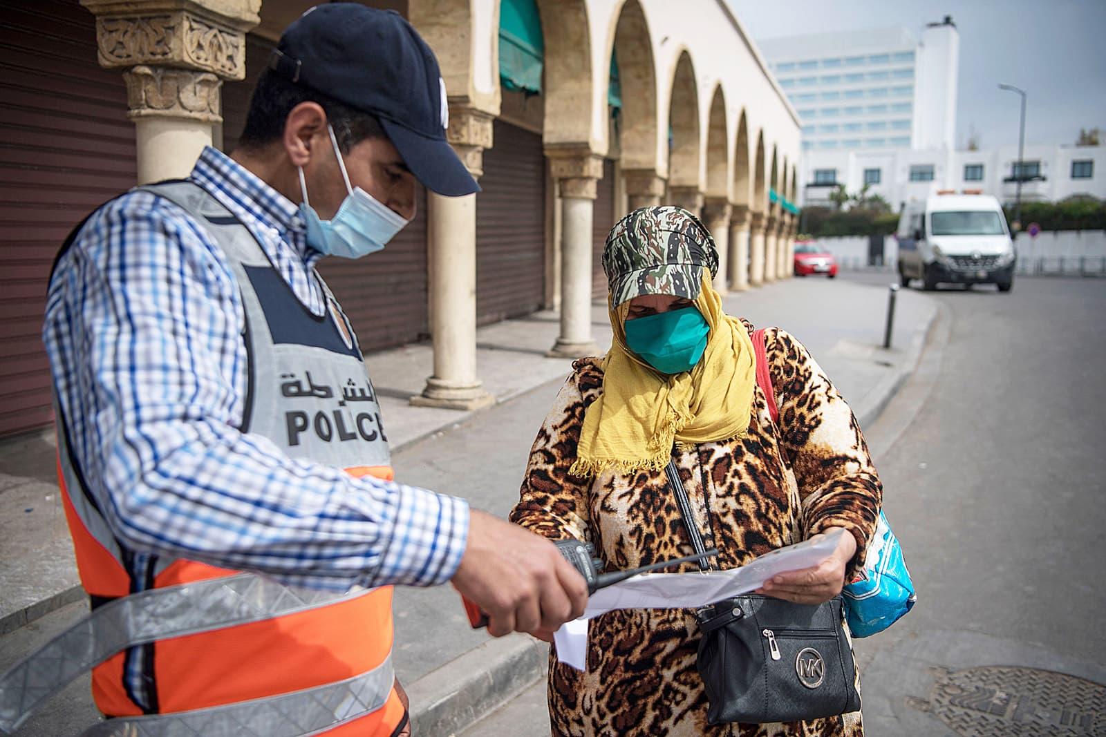 Un treballador oficial comprova que una dona tingui permís per circular per Casablanca, el 8 d'abril. Fotografia de Fadel Senna/AFP
